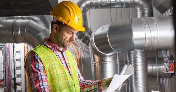 HVAC worker reading plans